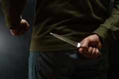 Criminal with knife weapon hidden behind his back stock photo