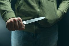 A criminal with a knife weapon threatens to kill. Criminality, crime, robbery thug.  stock photography