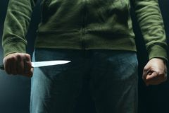 A criminal with a knife weapon threatens to kill. Criminality, crime, robbery thug.  stock photos