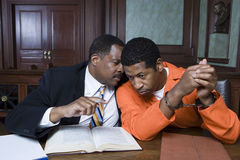 Criminal With Lawyer In Court. Advocate in discussion with criminal in the courtroom Stock Photo
