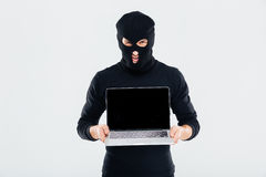 Criminal man in balaclava holding blank screen laptop Royalty Free Stock Images