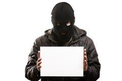 Criminal man in balaclava or mask covering face holding blank wh. Criminal man in balaclava or mask covering face hand holding blank card white isolated Stock Photos