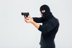 Criminal man in balaclava standing and aiming with gun Stock Image