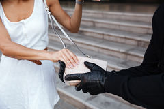 Criminal man in gloves stealing woman bag outdoors Royalty Free Stock Photos