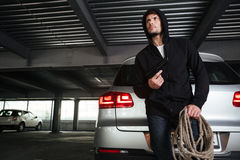 Criminal man with gun and rope standing on car parking Stock Photography