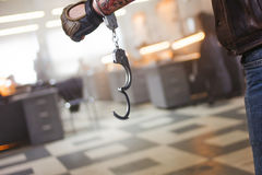 Criminal man. Hand male in unbuttoned handcuffs, on background of the police station Royalty Free Stock Photos