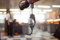 Criminal man. Hand male in unbuttoned handcuffs, on background of the police station Stock Image