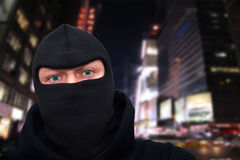 Criminal man with a mask standing on a street at night Royalty Free Stock Image
