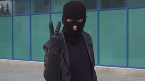 Criminal man thief or robber in mask counts up to three. Portrait of man in balaclava outdoor.  stock video