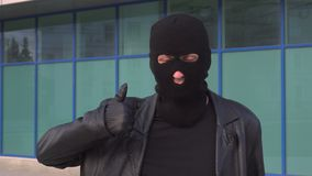 Criminal man thief or robber in mask shows thumb up. Portrait of man in balaclava stock video