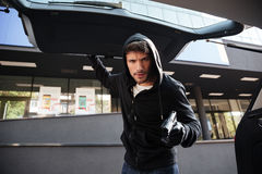 Criminal man threatening with gun and closing car trunk outdoors Royalty Free Stock Photo