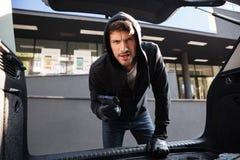 Criminal man threatening with gun and looking at car trunk Royalty Free Stock Image