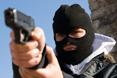 Criminal in mask aiming his target. Armed criminal man targeting with a semi-automatic pistol Stock Photo