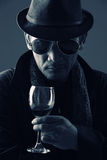 Criminal mastermind and a glass of wine Royalty Free Stock Photography