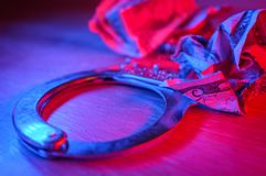 Criminal Money Concept. Conceptual handcuffs with crumpled dollar bills and police lights stock image