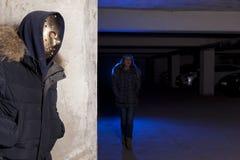 Criminal que lleva una máscara que espera a una mujer Foto de archivo