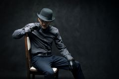 The criminal and robber in black gloves are sitting on a chair royalty free stock photography