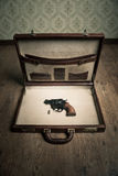 Criminal's briefcase. Open vintage leather briefcase with only revolver gun and bullet inside, vintage wallpaper and wooden floor on background stock images