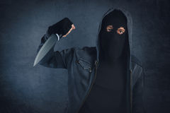 Criminal with sharp knife threating, victim's point of view Stock Photo