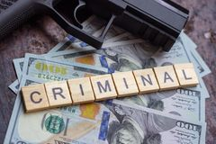 Criminal sign and black gun on usa dollars background. Black market, contract killing, mafia and crime concept stock image