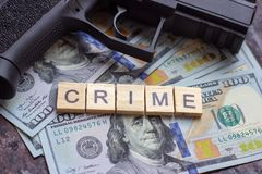 Criminal sign and black gun on usa dollars background. Black market, contract killing, mafia and crime concept.  stock photography