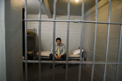 Criminal Sitting On Bed In Jail Royalty Free Stock Photos