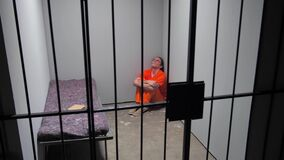 The criminal is sitting in the cell on the floor