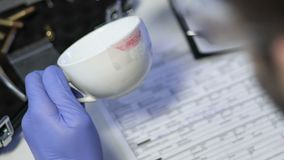 Criminal specialist taking lipstick print from white cup from murder scene