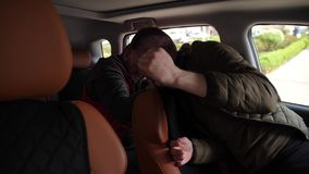Criminal strangling driver with seat belt in car. Close-up of thug suffocating man sitting in driver`s seat with safety belt using it as noose. Male driver stock footage