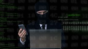 Criminal in suit and balaclava breaking security code using laptop and phone. Stock footage stock footage
