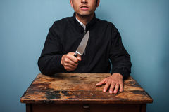 Criminal at table waving a knife Stock Photo