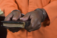 Criminal Taking Oath. Criminal holding bible takes an oath in courtroom Stock Images