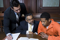 Criminal With Two Lawyers. Criminal sitting with two lawyers in the courtroom Stock Image