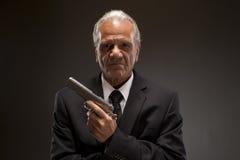 Criminal u hombre de negocios con la arma de mano Imagenes de archivo