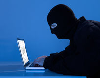 Criminal Using Laptop To Hack Data At Table Royalty Free Stock Image