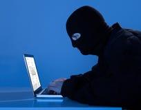Criminal Using Laptop To Hack Data At Table Royalty Free Stock Image