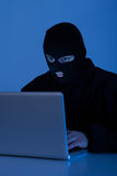 Criminal Using Laptop To Hack Online Account Stock Photo