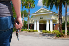 Criminal w gun bank robbery crime. A criminal with a pistol gun is standging outside of a bank as he prepares to commit bank robbery and rob them of large Royalty Free Stock Photo