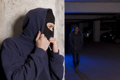 Criminal wearing a mask waiting for a woman Stock Images