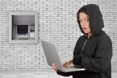 Criminal Woman Hacker Wearing Hood On Using a Laptop in front of. Build In Bank Cash ATM Machine extreme closeup Stock Image