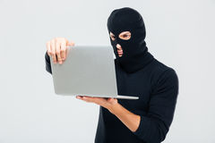 Criminal young man in balaclava standing and using laptop Stock Image