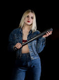 Criminal young woman with baseball bat, young hooligan in jeans and a denim jacket Stock Image