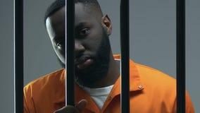 Criminale afroamericano colpevole che esamina macchina fotografica attraverso le barre della prigione, giudizio video d archivio