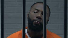 Criminale afroamericano sicuro in cella di prigione che esamina macchina fotografica con disprezzo video d archivio