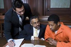 Criminale con due avvocati immagine stock