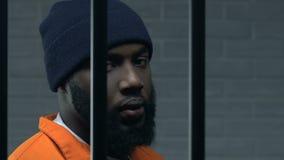 Criminale nero che tiene aggressivamente le barre della prigione e che esamina macchina fotografica, colpevole video d archivio