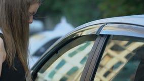 Criminale non identificato maleducato che attacca donna vicino all'auto, minacciosa lei, il pericolo archivi video