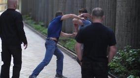 Criminales armados que paran al hombre joven en la calle secundaria almacen de metraje de vídeo