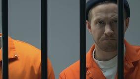Criminali multietnici imprigionati in prigione, esaminante macchina fotografica attraverso le barre, colpevoli archivi video