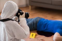 Criminalist photographing dead body at crime scene. Murder, investigation, forensic examination and people concept - criminalist with camera photographing dead Royalty Free Stock Images